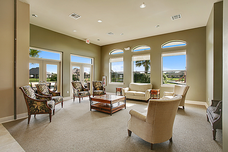 The large sitting area in the community center has views of the pool area and homes along the lake.